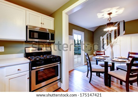 Bright kitchen room with white wood cabinets well matched with olive