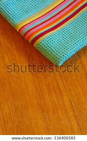 Bright kitchen towel on the wooden table - stock photo