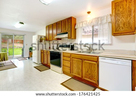 Bright kitchen with wood cabinets, tile floor, white appliances. Small dining area with walkout deck