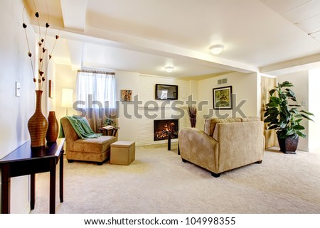 Bright large basement living room with fireplace and sofa. - stock photo