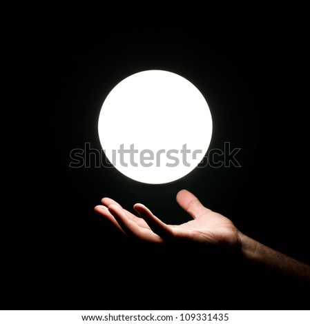 Bright light ball over human hand isolated on black background - stock photo