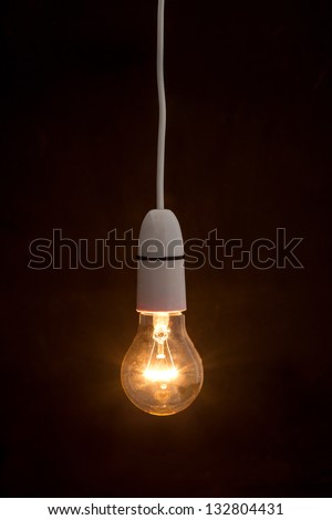 Bright light bulb turned on over black background - stock photo