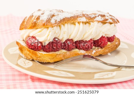 Bright light from behind creamy perfection of raspberry eclaire on dessert plate with fork.