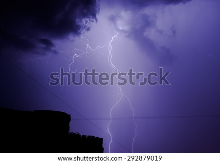 Bright lightning strike at night with thunder clouds overhead - stock photo