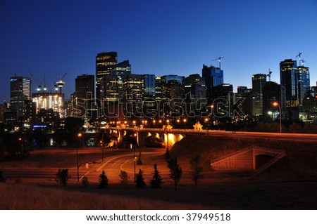 Bright lights, big city - downtown Calgary, Alberta, Canada at night. Bow Tower under construction can be seen on the left. - stock photo