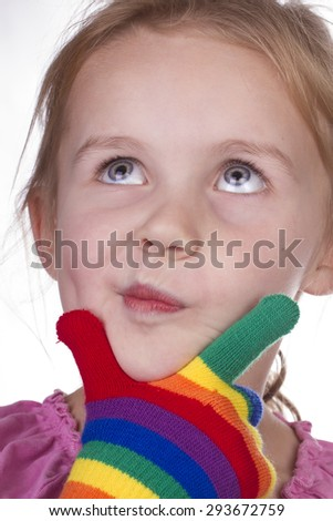 Bright little girl wearing colourful gloves and pulling funny faces for the camera