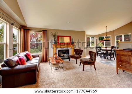Bright living room with beige carpet floor, leather couch, coffee table and antique style chairs, fireplace and cabinet. Living room open to vaulted ceiling dining area - stock photo