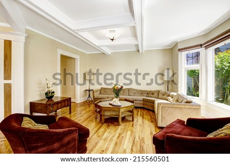 Bright living room with coffered ceiling system, hardwood floor and round window