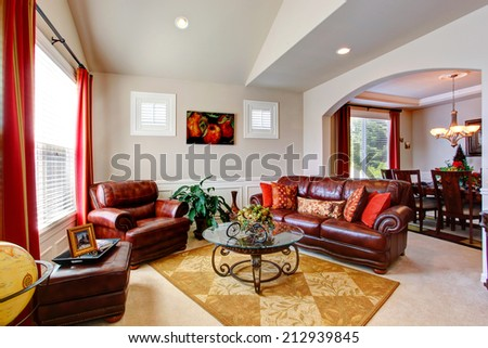 Bright living room with leather couches and glass top coffee table in luxury house