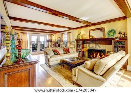 Bright living room with rustic furniture, ceiling beams, fireplace and walkout deck - stock photo