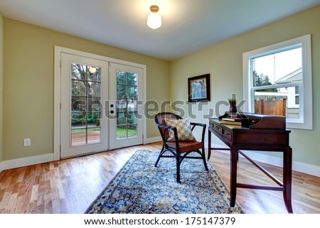 Bright living room with walkout deck furnished with antique desk and rustic chair. - stock photo