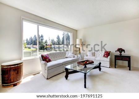 Bright living room with white carpet floor and furniture set. View of glass top coffee table and antique dram - stock photo