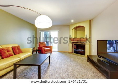 Bright living room with yellow and orange couch and chair, dark brown wood coffee table, carpet floor, tv , cozy fireplace and arch niche above it. - stock photo