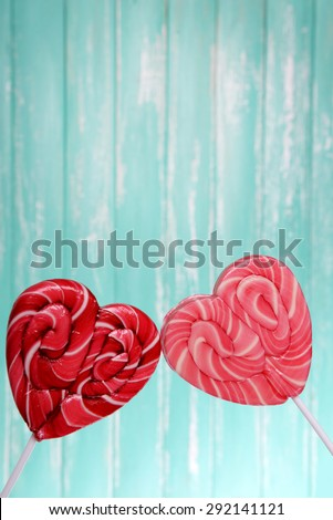 Bright lollipops in shape of heart on wooden background - stock photo