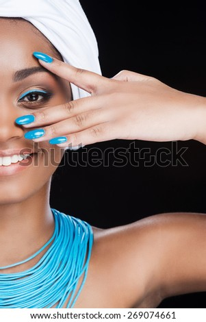 Bright look. Cropped picture of a beautiful African woman wearing a headscarf and smiling while looking at camera and standing against black background - stock photo