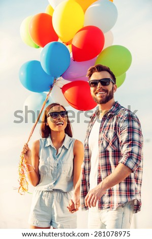 Bright love. Cheerful young couple holding hands and smiling while walking outdoors with colorful balloons - stock photo