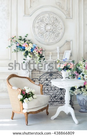 Bright luxury white and blue colored interior living room with flowers in vases. the walls are decorated with baroque ornaments.