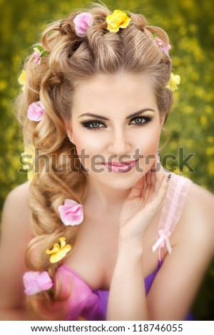 Bright make-up woman at blossom field. Alluring blond girl with professional make up and gorgeous fantasy hairstyle with fresh flowers posing outdoor. Sexy young lady with flowers. Spring concept. - stock photo