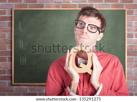 Bright male school teacher holding alphabet letter Q in school classroom with copyspace blackboard. Education question conceptual. - stock photo
