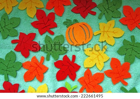 Bright Maple leaves out of felt on a light green fabric as a background                                - stock photo