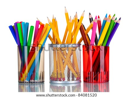 Bright markers and crayons in holders isolated on white