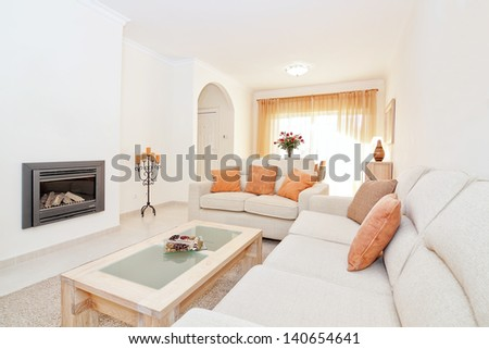 Bright modern living room with a fireplace for heating. In the warm colors. - stock photo