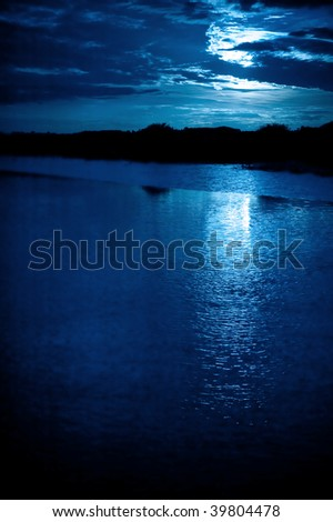 bright moonlight and cloudscape over coastline water - stock photo