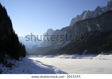 Bright morning light shines on a frozen lake surrounded by mountains