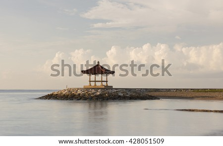 Bright morning light shinning on the shore with a gazebo.  Fresh air and calm wave by the beach.  Clear blue sky and puffy cotton white cloud.