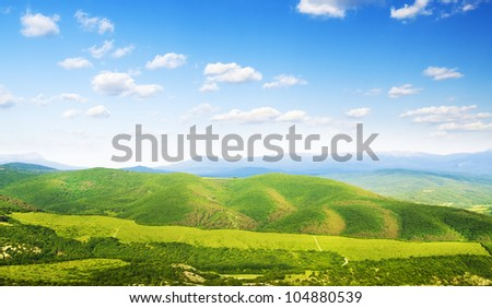 Bright mountains  hills. Bright sky and clouds