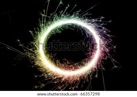 bright multi colored circle of glowing sparks on a black background - stock photo