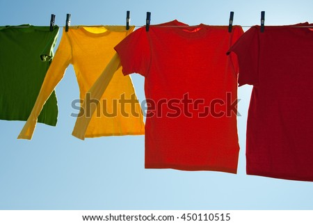 Bright multi-colored clothes drying in the wind, on a sunny day.