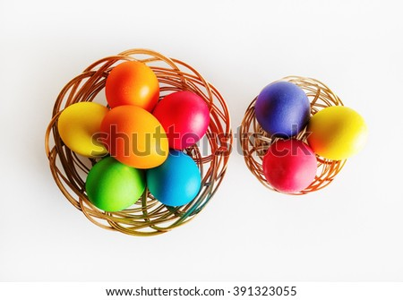 Bright multi-colored easter eggs in two baskets. Colorful easter eggs. Top view. - stock photo