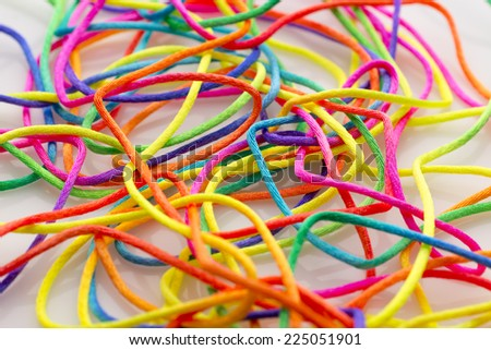 Bright multi-colored threads on a white background.