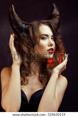bright mysterious woman with horn hair, halloween celebration close up - stock photo