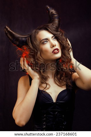 bright mysterious woman with horn-shaped hair, halloween celebration close up - stock photo