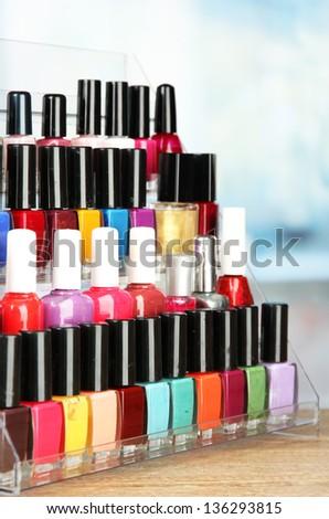 Bright nail polishes on shelf in beauty salon - stock photo