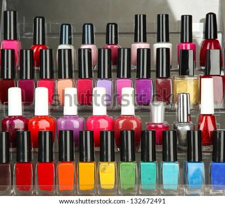 Bright nail polishes on shelf on grey background - stock photo
