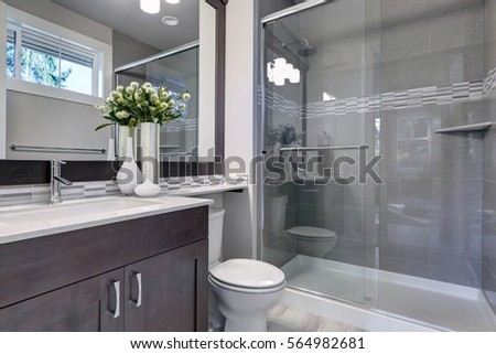 Bright New Bathroom Interior With Glass Walk In Shower With Grey Tile  Surround, Brown Vanity