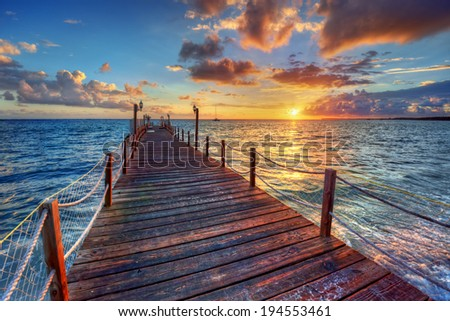 Bright ocean pier sunrise with colorful clouds over azure waters - stock photo