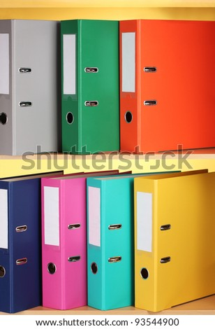 bright office folders on wooden shelfs on yellow background