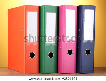 bright office folders on wooden table on yellow background