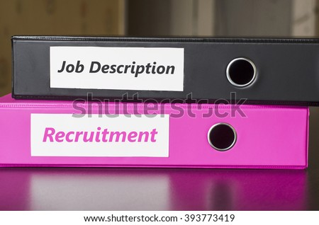 Bright office folders over dark background and job description and recruitment text concept - stock photo