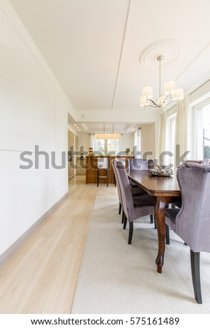 Bright Open Plan Dining Room With Long Table Next To Modern Kitchen