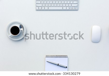 Bright Open Space Office White Table Top View with Coffee Mug Opened Blank Notepad Pen and Computer Keyboard and Mouse on Desk - stock photo
