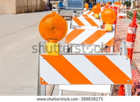 Bright orange and white striped construction warning barricades with warning lights lined up one behind the other.Shallow depth of field,selective focus on front traffic barrier.Blurred background  - stock photo