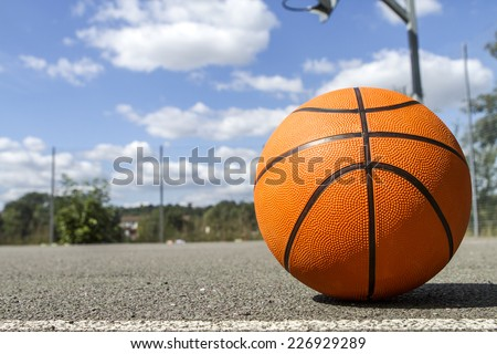 Bright orange basketball in the foreground on an outdoor basketball court on a sunny day with clouds in the background in the sky - stock photo