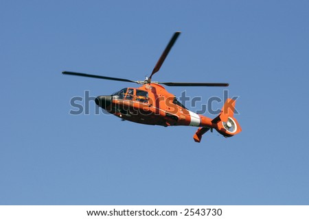 Bright Orange Coast Guard rescue Helicopter in flight against a blue sky