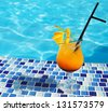Bright orange cocktail stands on edge of pool - stock photo
