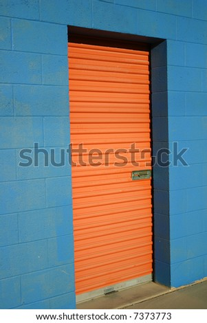 Bright orange door to storage unit in bright blue building
